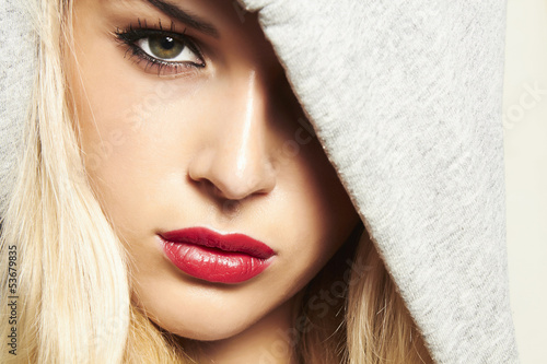 beautiful blond woman in hood. red lips.one eye