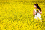 Beautiful Woman in white dress holding a bunch of rape flowers.