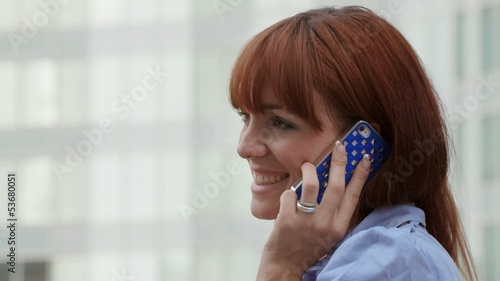 Happy businesswoman talking on mobile phone near office building