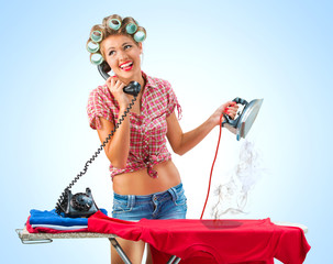 Housewife talking on the phone while ironing, blue background