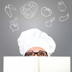 Woman in chef's hat looking over cookbook at drawn ingredients