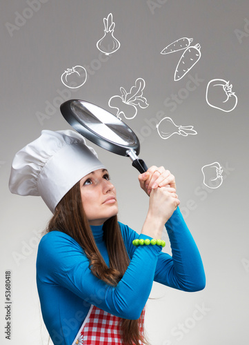 Woman with pan protecting herself from falling drawn vegetables