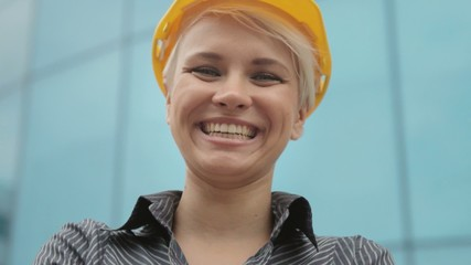 Portrait of female engineer with helmet smiling at camera