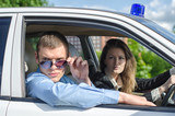 Two young detectives driving to crime scene.