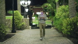 Young man walking in tourist resort at night with cellphone