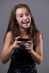 A young teenager laughing about a message