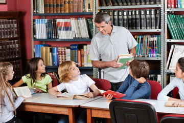 Teacher Communicating With Students Sitting At Table In Library