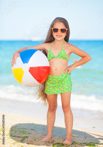 child with sunglasses and ball at the beach