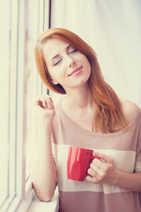 Beautiful young woman with cup over window.