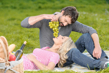 Lovely moments. Young men feeding his girlfriend with a grapes b