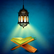 Hanging illuminated arabic lamp and open holy book Quran on blue