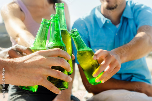 Friends cheers their beers at a party