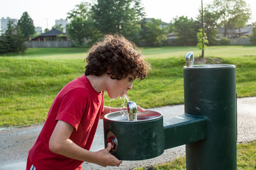 Child drinking from a water fountain
