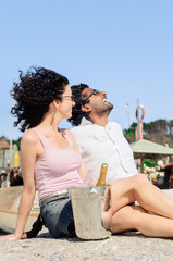 Couple enjoying themselves by the sea with champagne sparking wi