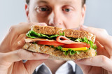 Close up of a business man eating a healthy sandwich