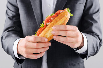 Businessman holding a lunch roll, eating on the go