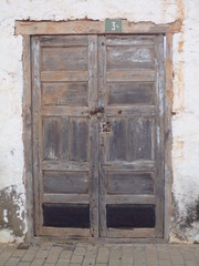 Rustic flaky Black door in Fuerteventura with flaky plaster