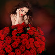 Young beautiful woman with red roses bouquet over flowers