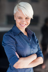 Businesswoman wearing shirt and smiling in front of a dark backg