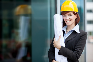 Smiling female constructor next a glass building