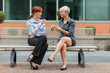 Businesswoman sitting outside on a bench and talking