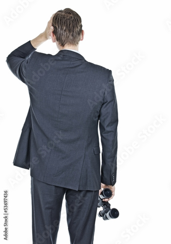 Businessman looking worried and holding binocular