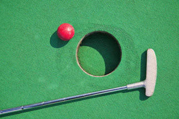 Close-up of miniature golf hole with bat and ball