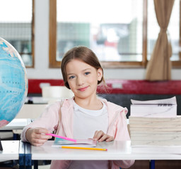Cute Girl Smiling With Books And Globe At Desk