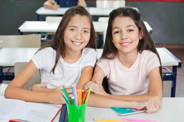Schoolgirls Sitting At Desk In Classroom