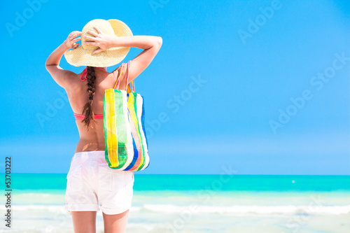 Woman in straw hat and on a tropical beach with bag