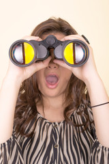 cute woman holding binoculars, yellow background