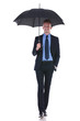 business man walks with umbrella