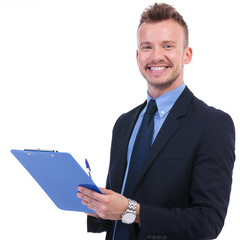 business man smiles with pen and clipboard