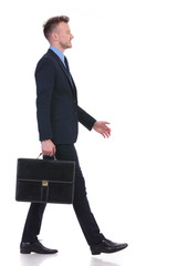 business man walks to side with briefcase