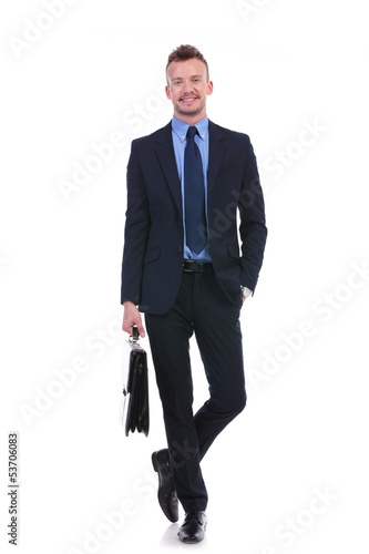 business man stands with suitcase and hand in pocket