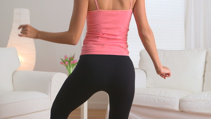 Rear view of woman dancing in yoga pants