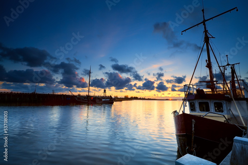 fishing boats on river at sunset