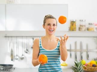 Happy young woman joggling with oranges in kitchen