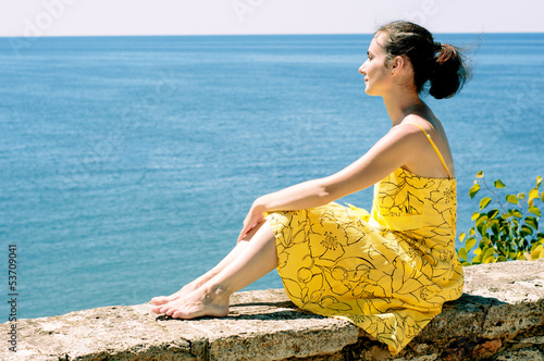 Beautiful young woman admiring the sea