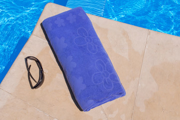 Blue towel and sunglasses near the pool