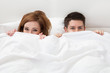 Portrait of young couple hiding face with blanket