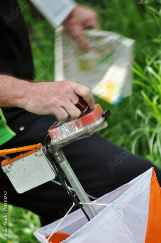 A man punching at the orienteering control point close up