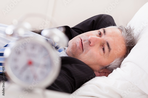 Alarm Clock In Front Of Man Sleeping