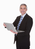 Happy Mature Businessman Using Laptop