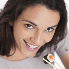 frau laechelt in die Kamera mit Sushi auf Staebchen