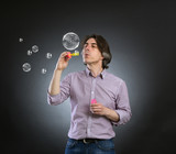 A man inflates soap bubbles.