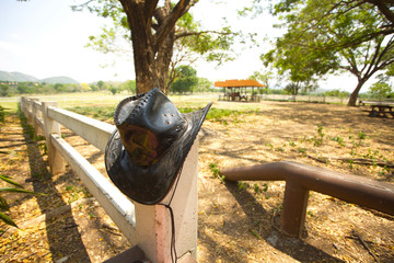 cowboy hat, black cowboy hat hanging on farm fence