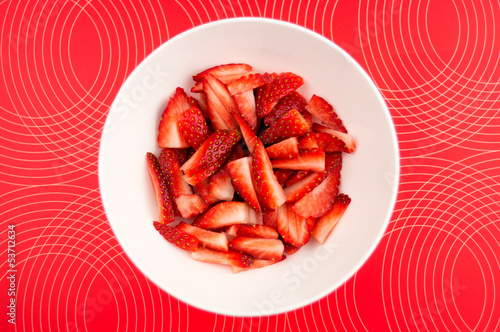 Chopped strawberries in a bowl against a patterned background
