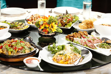 meal time, full round table with colorful food in restaurant