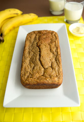 Banana bread with bananas, milk and butter in the background